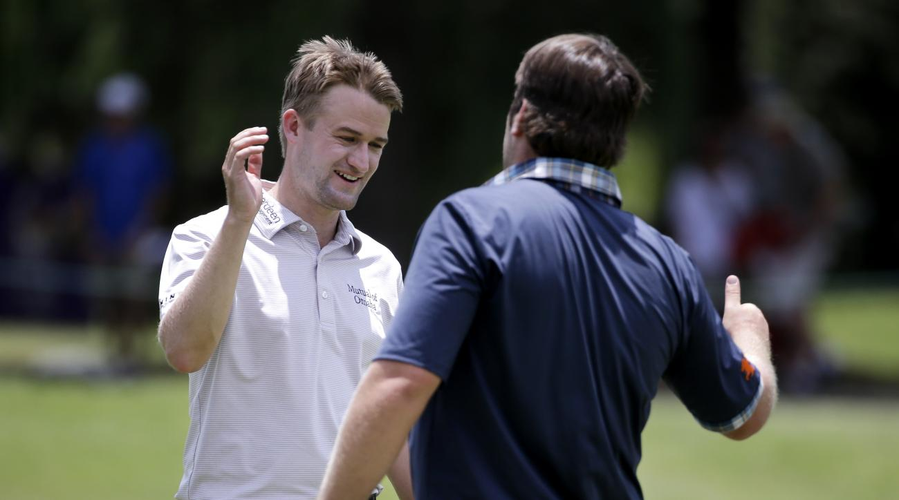 Russell Knox, left, of Scotland, shakes hands with playing partner Jim Renner on the ninth green following their second round of the St. Jude Classic golf tournament Friday, June 12, 2015, in Memphis, Tenn. (AP Photo/Mark Humphrey)