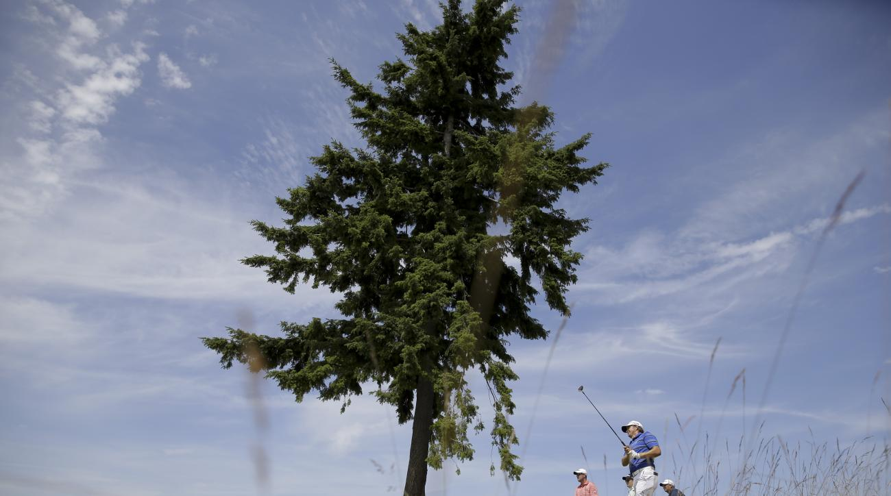Retief Goosen, of South Africa, watches his tee shot on the 17th hole as Marc Leishman, left, of Australia, looks on during a practice round for the U.S. Open golf tournament at Chambers Bay, Monday, June 15, 2015, in University Place, Wash. (AP Photo/Ted