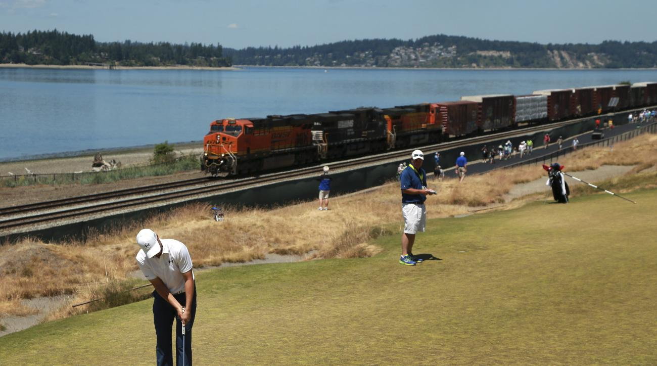 Jordan Spieth putts as a train goes by on the 16th hole during a practice round for the U.S. Open golf tournament at Chambers Bay on Wednesday, June 17, 2015 in University Place, Wash. (AP Photo/Charlie Riedel)