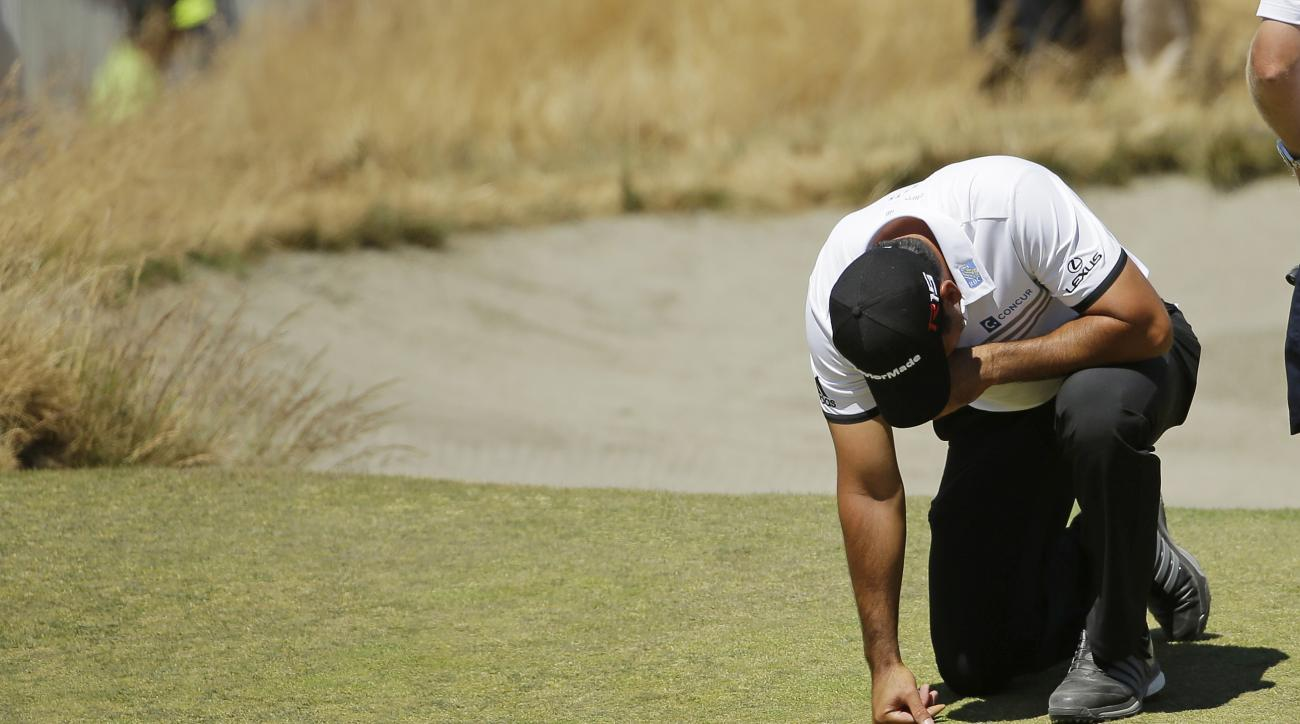 Jason Day, of Australia, kneels while waiting to putt on the ninth hole after having collapsed earlier in the fairway during the second round of the U.S. Open golf tournament at Chambers Bay on Friday, June 19, 2015 in University Place, Wash. (AP Photo/Te