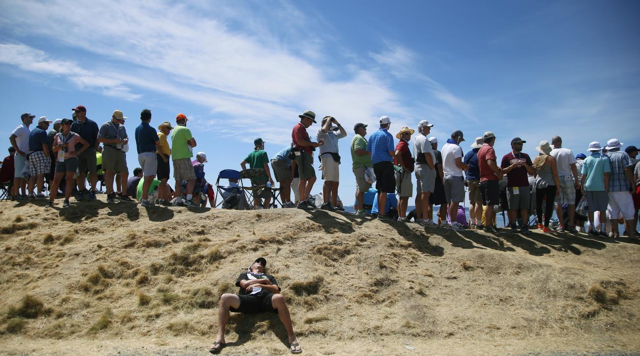 A fans takes a break near the second green during the final round of the U.S. Open golf tournament at Chambers Bay on Sunday, June 21, 2015 in University Place, Wash. (AP Photo/Lenny Ignelzi)