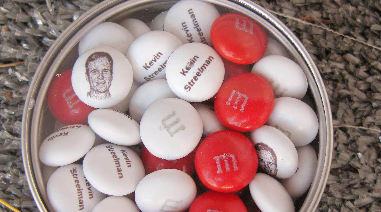 This personalized tin of M&M candies printed with the face and name of 2014 Travelers Golf Championship winner Kevin Streelman is seen Wednesday, June 24, 2015 in Cromwell, Conn. The tournament, which begins Thursday, has become known for the little perks