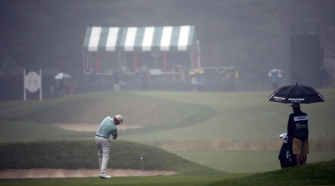 Davis Love III hits his second shot to a fog and rain shrouded 12th green during the second round of the Greenbrier Classic golf tournament at the Greenbrier Resort  in White Sulphur Springs, W.Va., Friday, July 3, 2015. Rain caused delays in play.  (AP P
