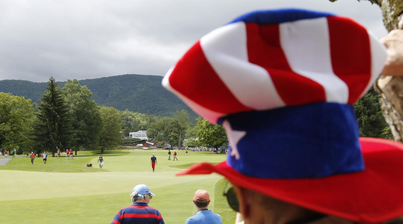 A fan with an Uncle Sam hat watches Tiger Woods, left, and Morgan Hoffmann, center, walk up to the first green during the third round of the Greenbrier Classic golf tournament at the Greenbrier Resort in White Sulphur Springs, W.Va., Saturday, July 4, 201