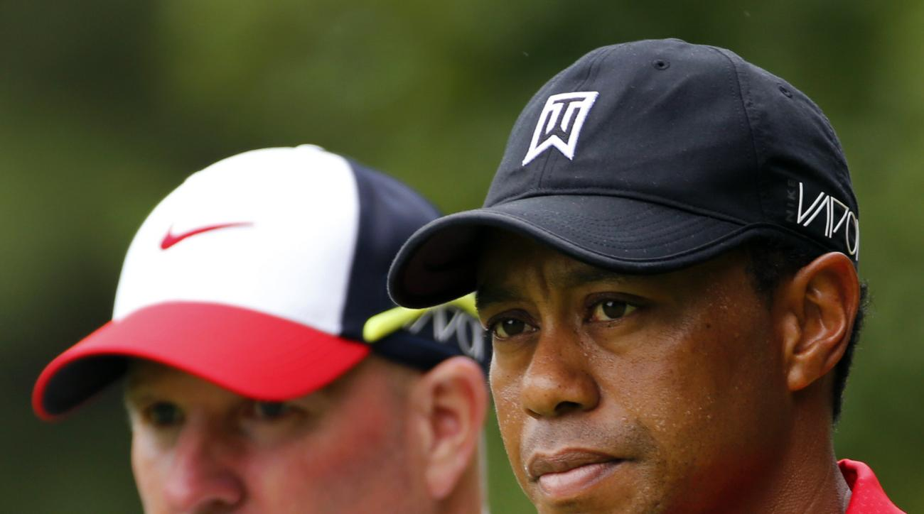 Tiger Woods and his caddie, Joe LaCava, left, walk off the 10th tee box during the final round of the Greenbrier Classic golf tournament, Sunday, July 5, 2015, at the Greenbrier Resort in White Sulphur Springs, W.Va. (AP Photo/Steve Helber)