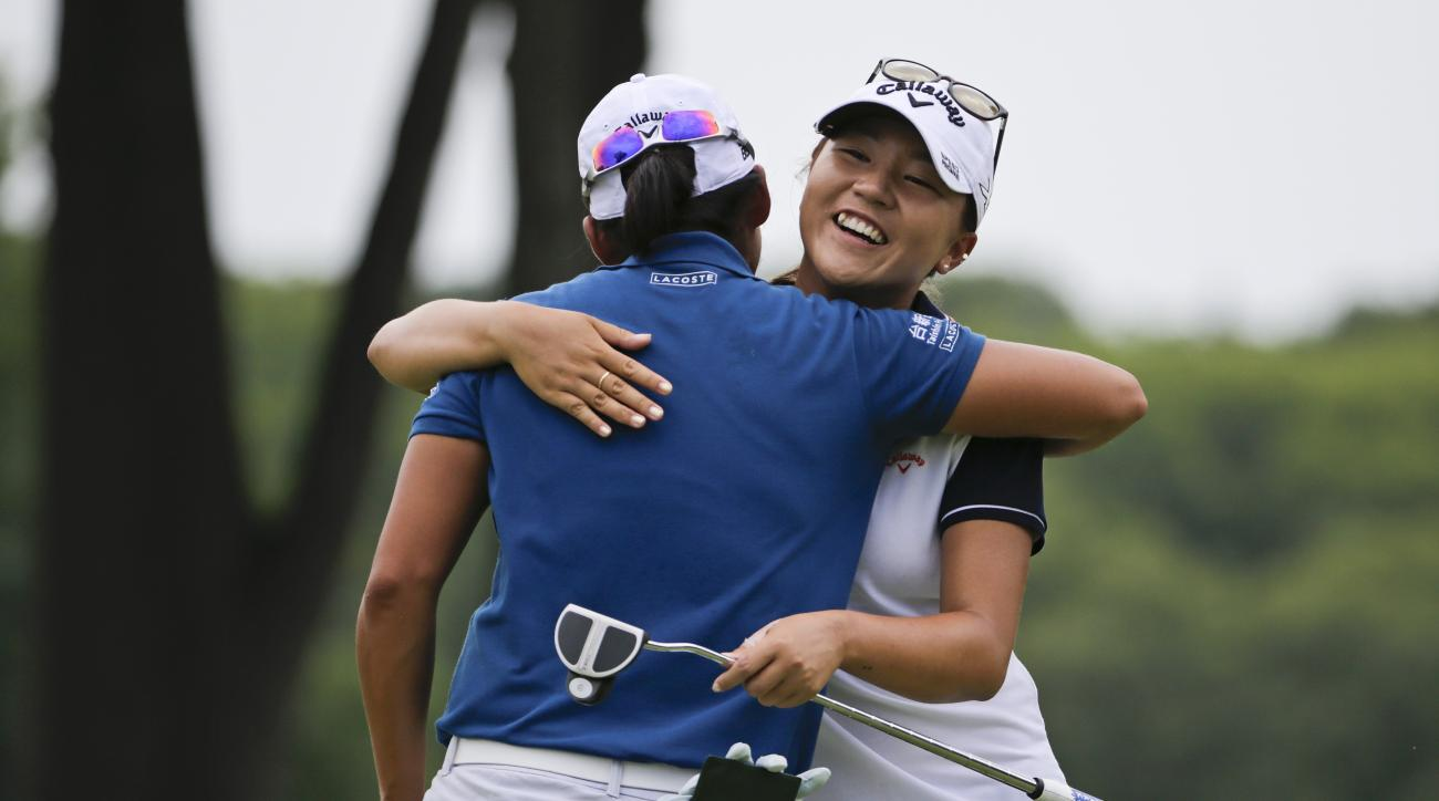 Lydia Ko, of New Zealand, hugs Taiwan's Yani Tseng at the ninth hole during a practice round for the U.S. Women's Open golf tournament at Lancaster Country Club, Wednesday, July 8, 2015, in Lancaster, Pa. (AP Photo/Frank Franklin II)