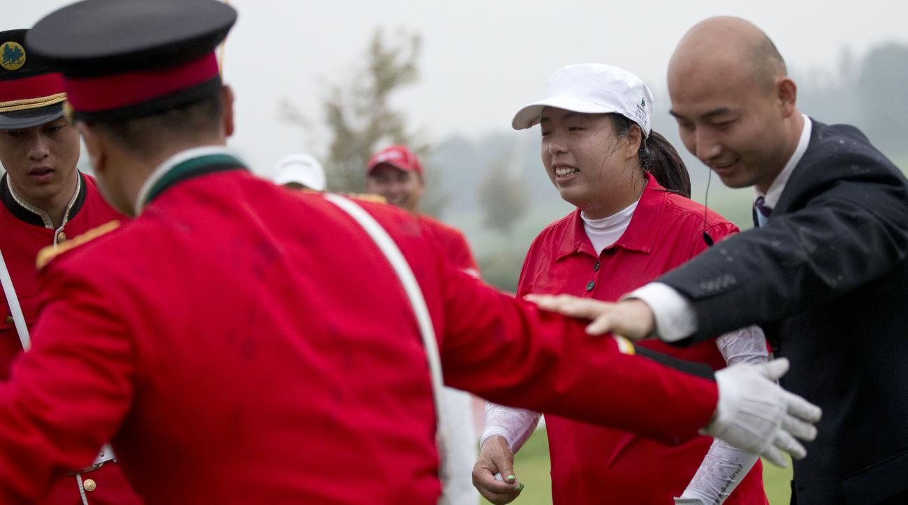 China's Feng Shanshan is escorted by security guards to leave the 18th green after she won the Reignwood LPGA Classic golf tournament at Pine Valley Golf Club on the outskirts of Beijing, China, Sunday, Oct. 6, 2013. (AP Photo/Alexander F. Yuan)