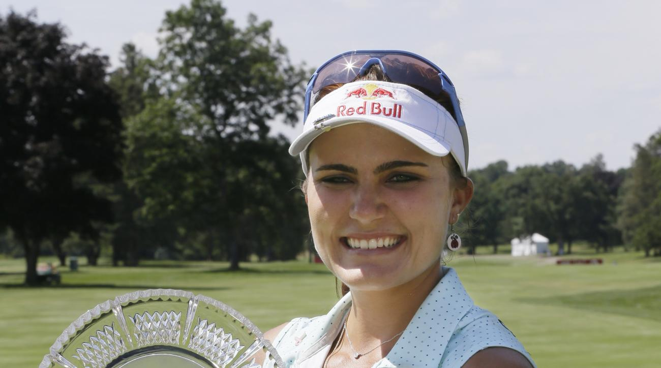 Lexi Thompson holds the trophy after winning the Meijer LPGA Classic golf tournament Sunday, July 26, 2015, in Belmont, Mich. (AP Photo/Carlos Osorio)