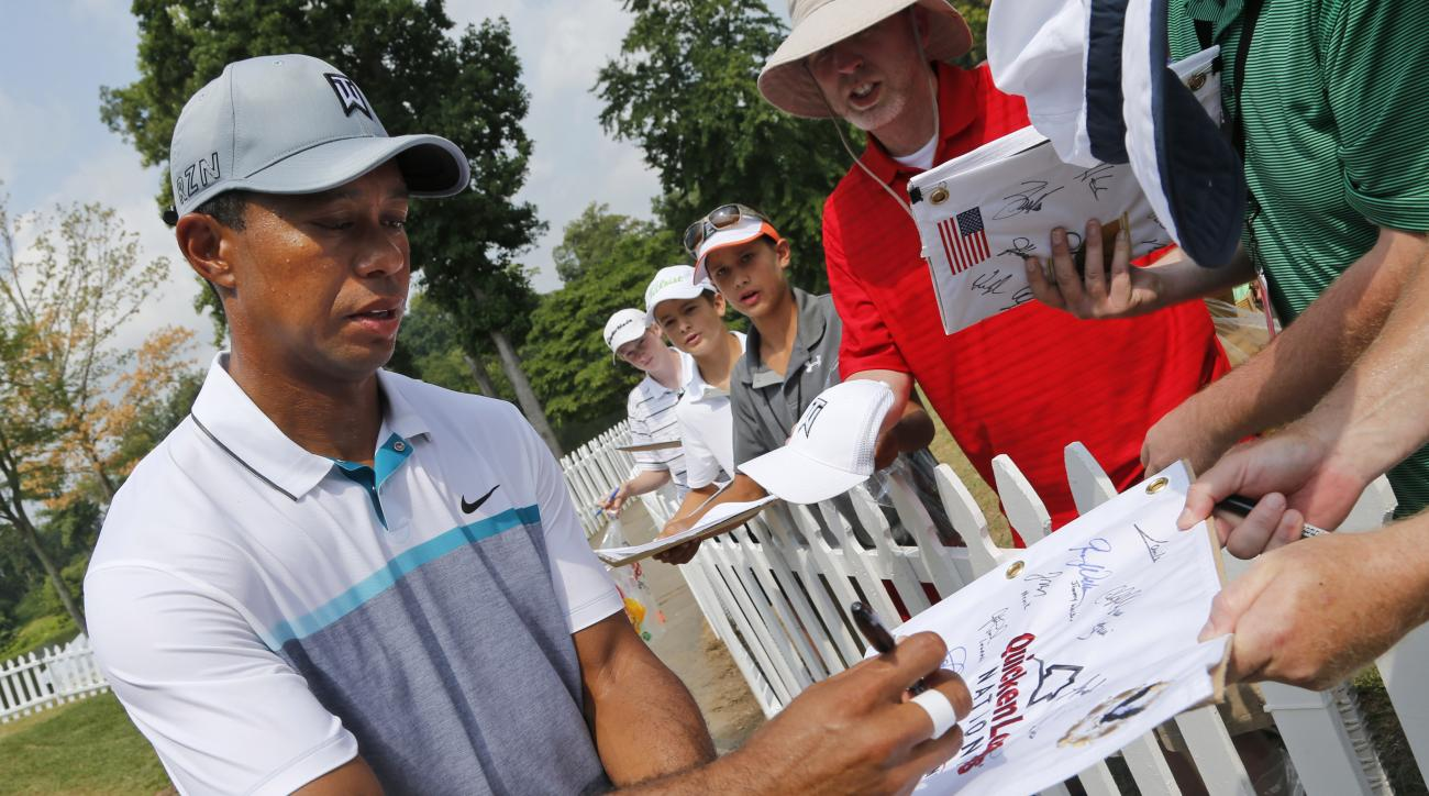 Tiger Woods signs autographs after a practice round for the Quicken Loans National golf tournament at the Robert Trent Jones Golf Club in Gainesville, Va., Tuesday, July 28, 2015.  (AP Photo/Steve Helber)