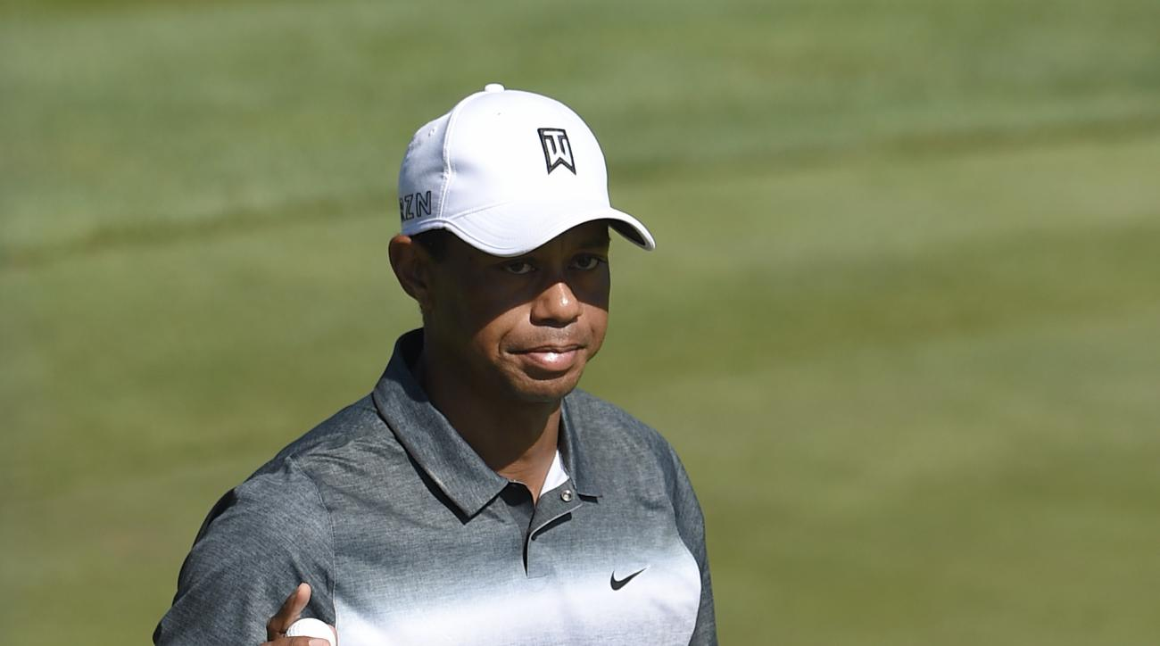 Tiger Woods shows the ball to the crowd on the 16th hole during the second round of the Quicken Loans National golf tournament at the Robert Trent Jones Golf Club in Gainesville, Va., Friday, July 31, 2015. (AP Photo/Nick Wass)
