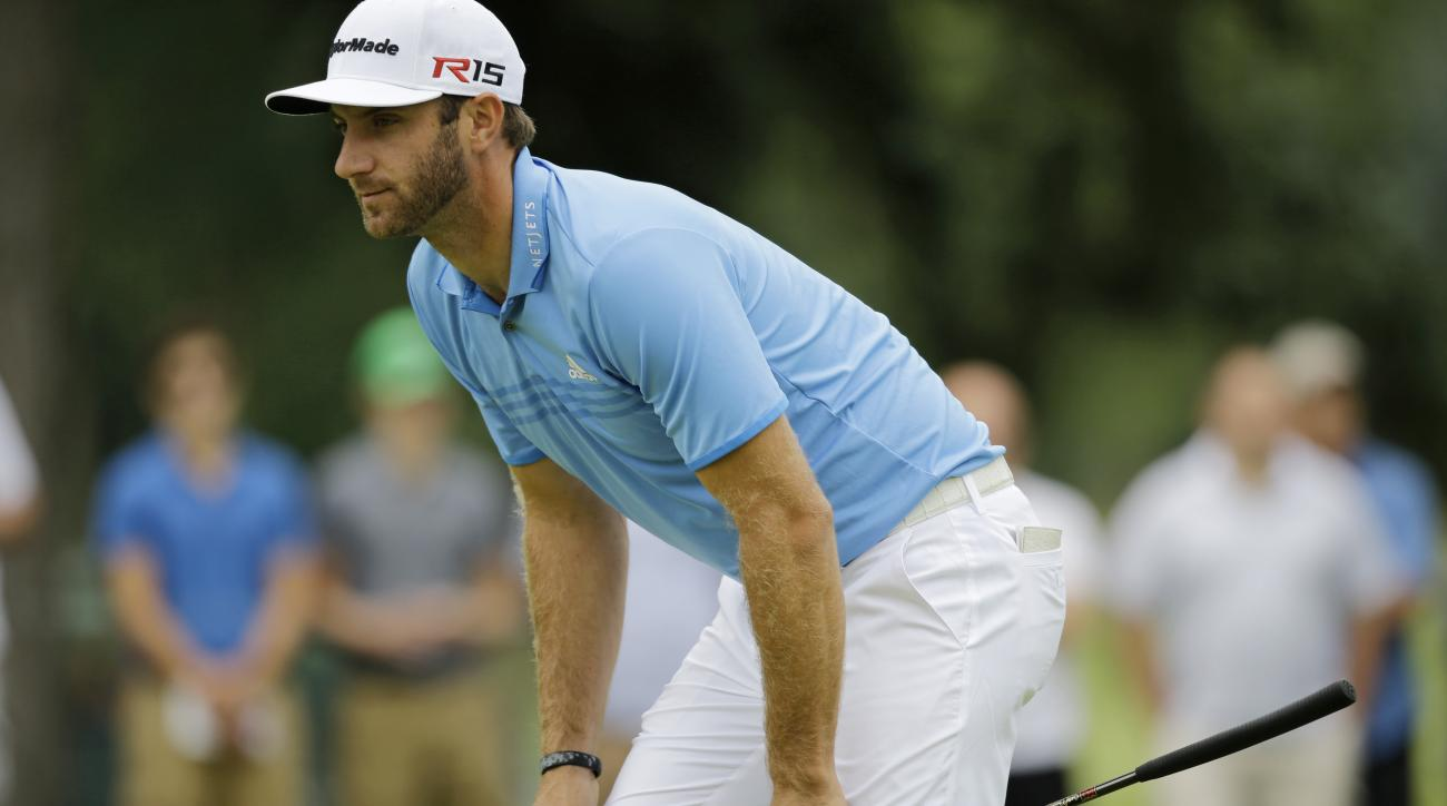 FILE - In this Aug. 6, 2015, file photo, Dustin Johnson sets up on the 11th green during the first round of the Bridgestone Invitational golf tournament at Firestone Country Club in Akron, Ohio. Johnson will not be able to ground his club in the same bunk