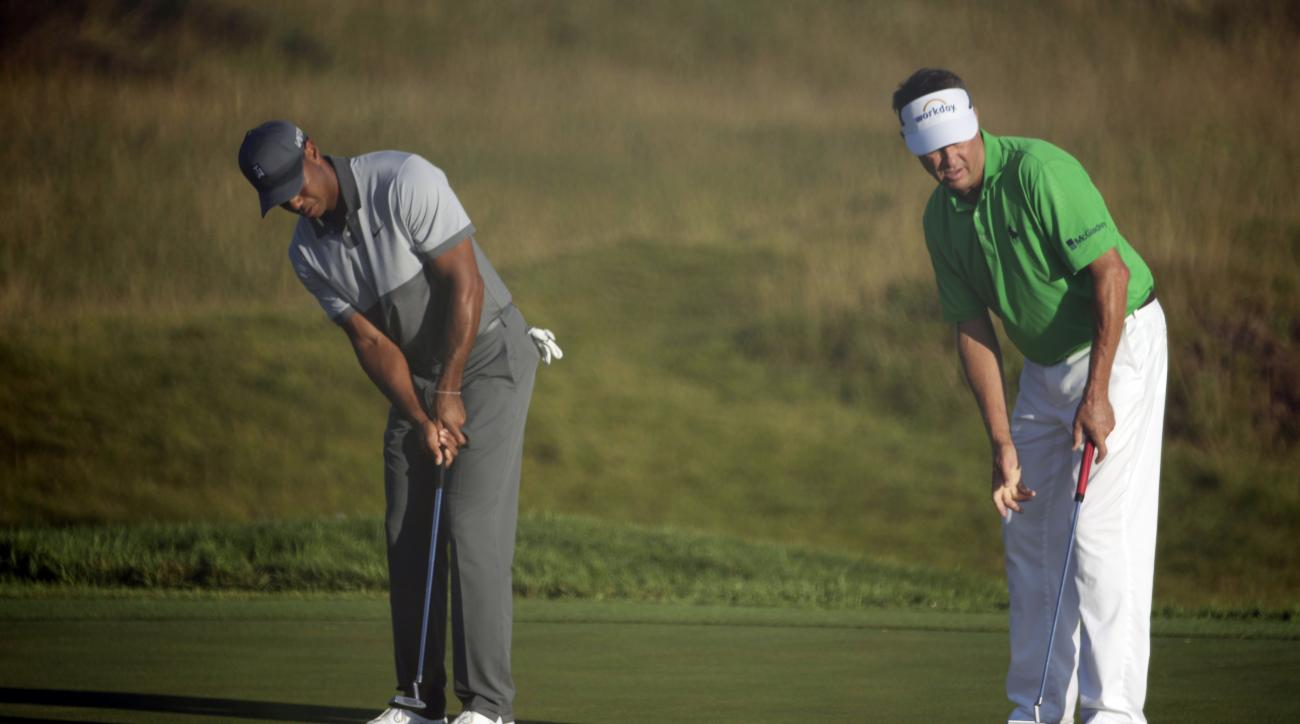Tiger Woods, left, and Davis Love III putt on the first green during a practice round for the PGA Championship golf tournament Tuesday, Aug. 11, 2015, at Whistling Straits in Haven, Wis. (AP Photo/Chris Carlson)