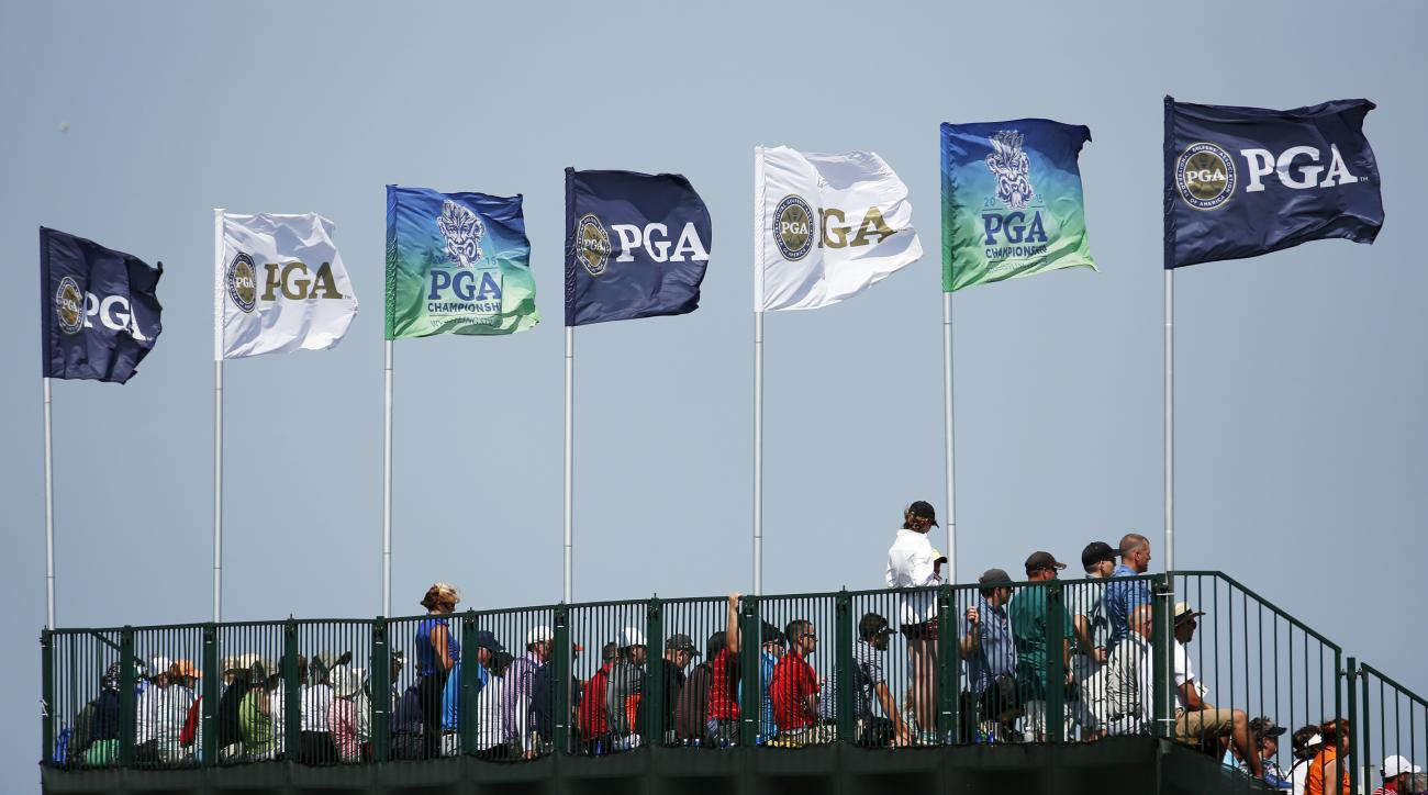 The flags are blowing as the wind picks up on the grandstands on the 12th hole during the first round of the PGA Championship golf tournament Thursday, Aug. 13, 2015, at Whistling Straits in Haven, Wis. (AP Photo/Julio Cortez)