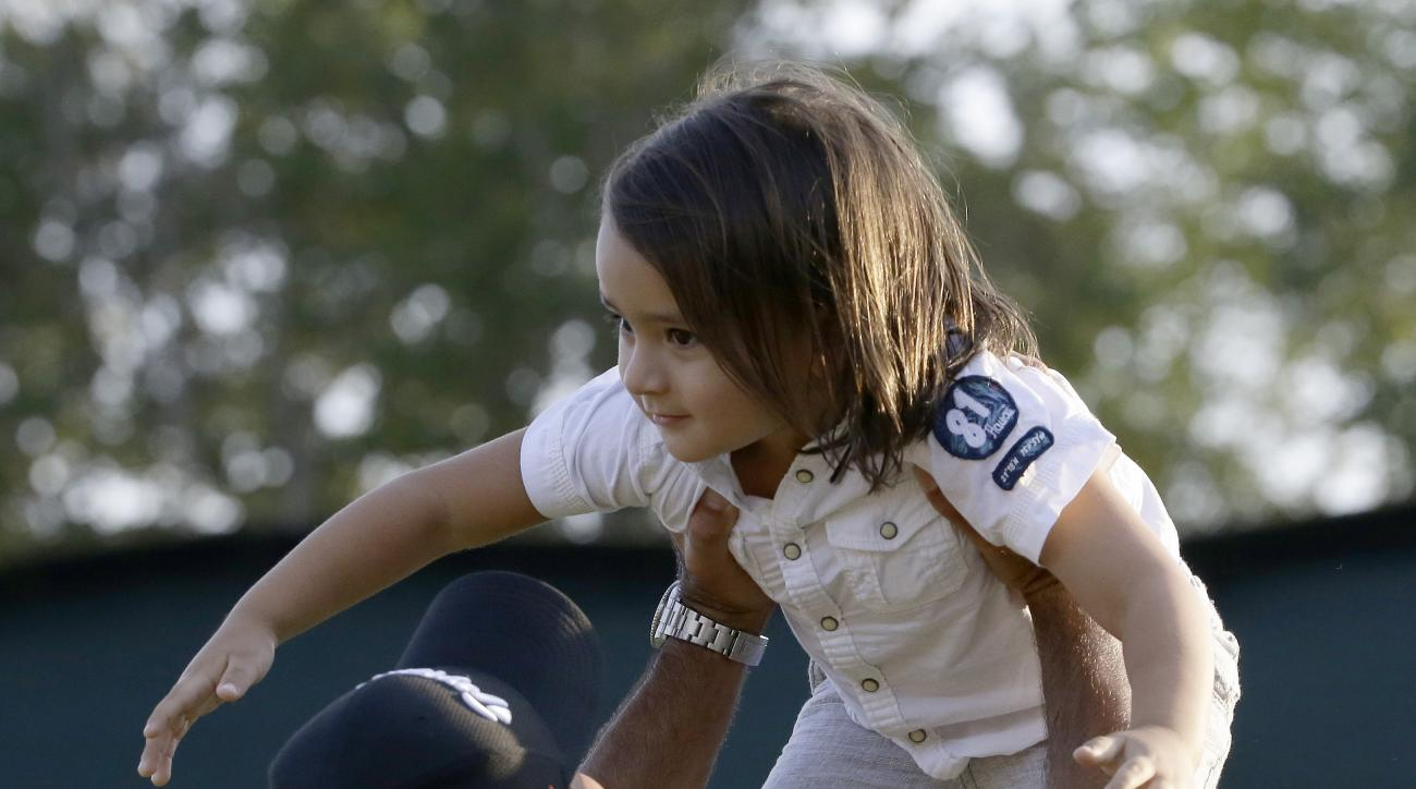 Jason Day, of Australia, holds up his son Dash after winning the PGA Championship golf tournament Sunday, Aug. 16, 2015, at Whistling Straits in Haven, Wis. (AP Photo/Brynn Anderson)