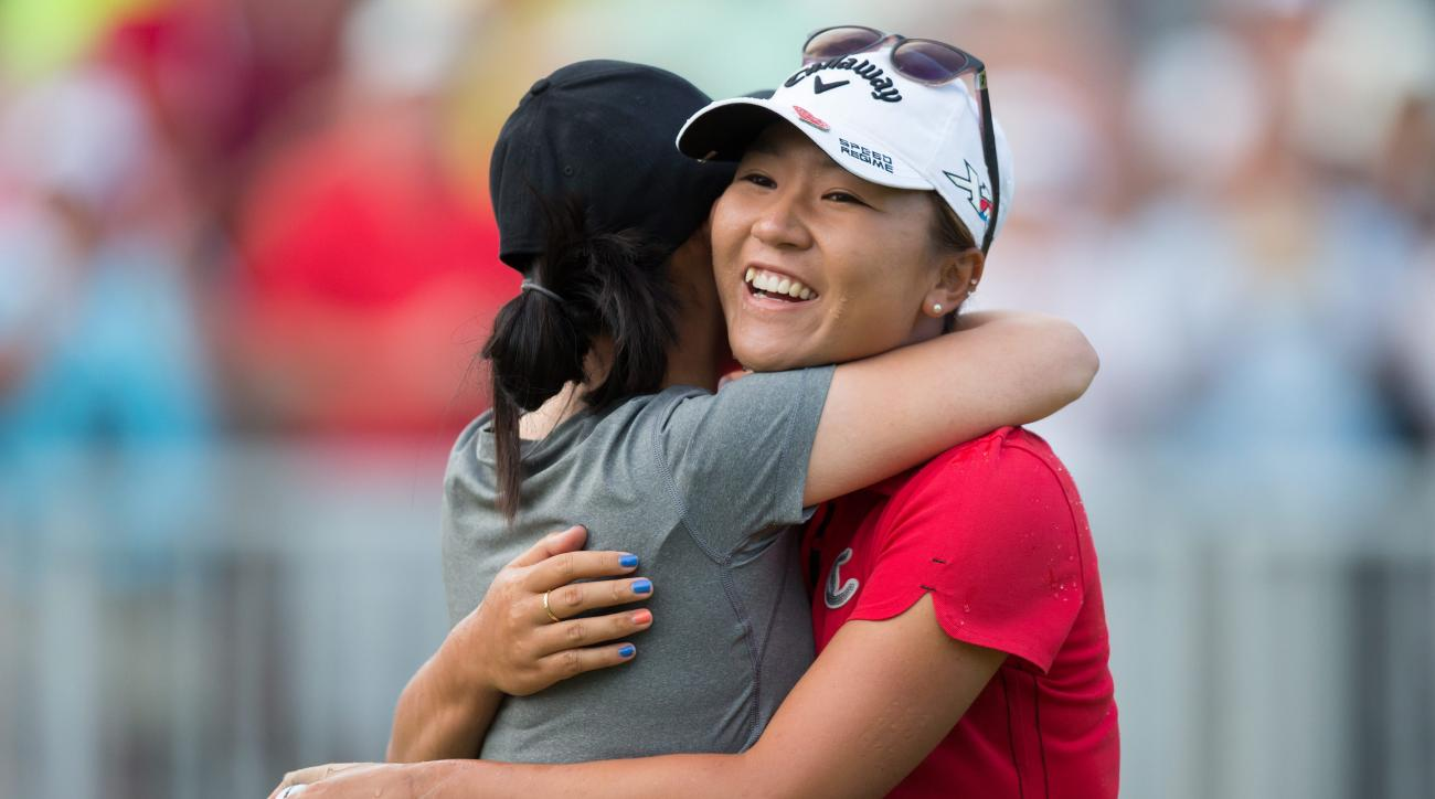 Lydia Ko, right, of New Zealand, hugs Sue Kim after Kim splashed her with water following Ko's win at the Canadian Pacific Women's Open golf tournament, in a playoff against Stacy Lewis, of the United States, at Vancouver Golf Club in Coquitlam, British C