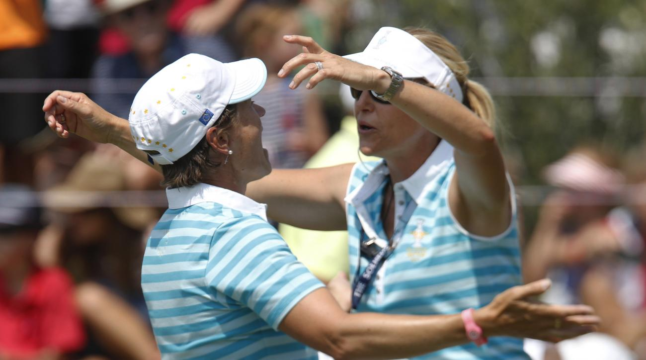Europe's Catriona Matthew, left, from Scotland, is congratulated by assistant captain Carin Koch, Sweden, after Matthew and Caroline Masson, from Germany, halved their foursome match at the Solheim Cup golf tournament against the United States, Saturday,