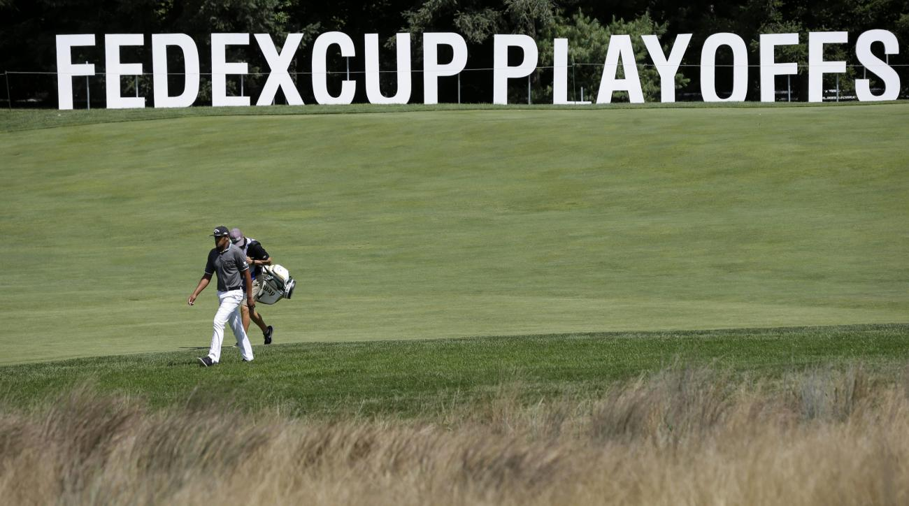 Tony Finau walks with his caddie Greg Bodine on the 18th hole during the second round of play at The Barclays golf tournament Friday, Aug. 28, 2015, in Edison, N.J. (AP Photo/Mel Evans)