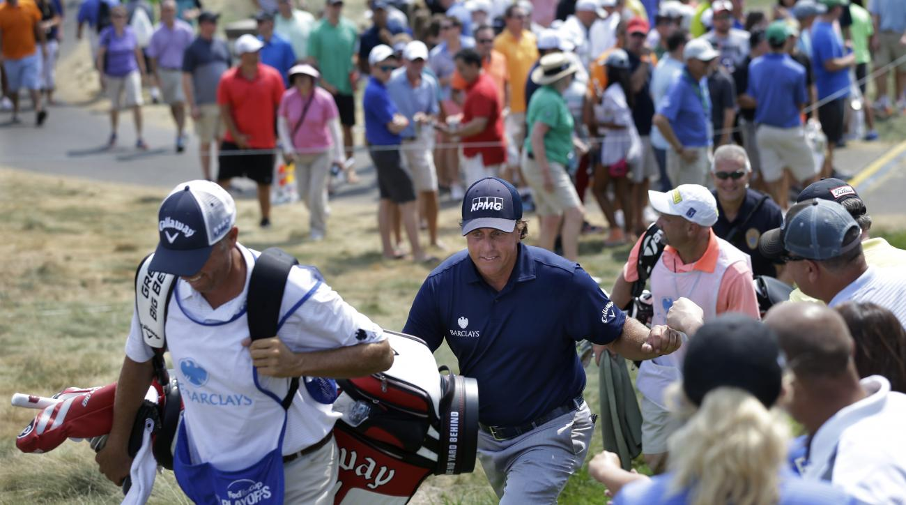 Phil Mickelson, center, bumps fists with fans as he walks to the ninth ole during the final round of play at The Barclays golf tournament Sunday, Aug. 30, 2015, in Edison, N.J. (AP Photo/Mel Evans)