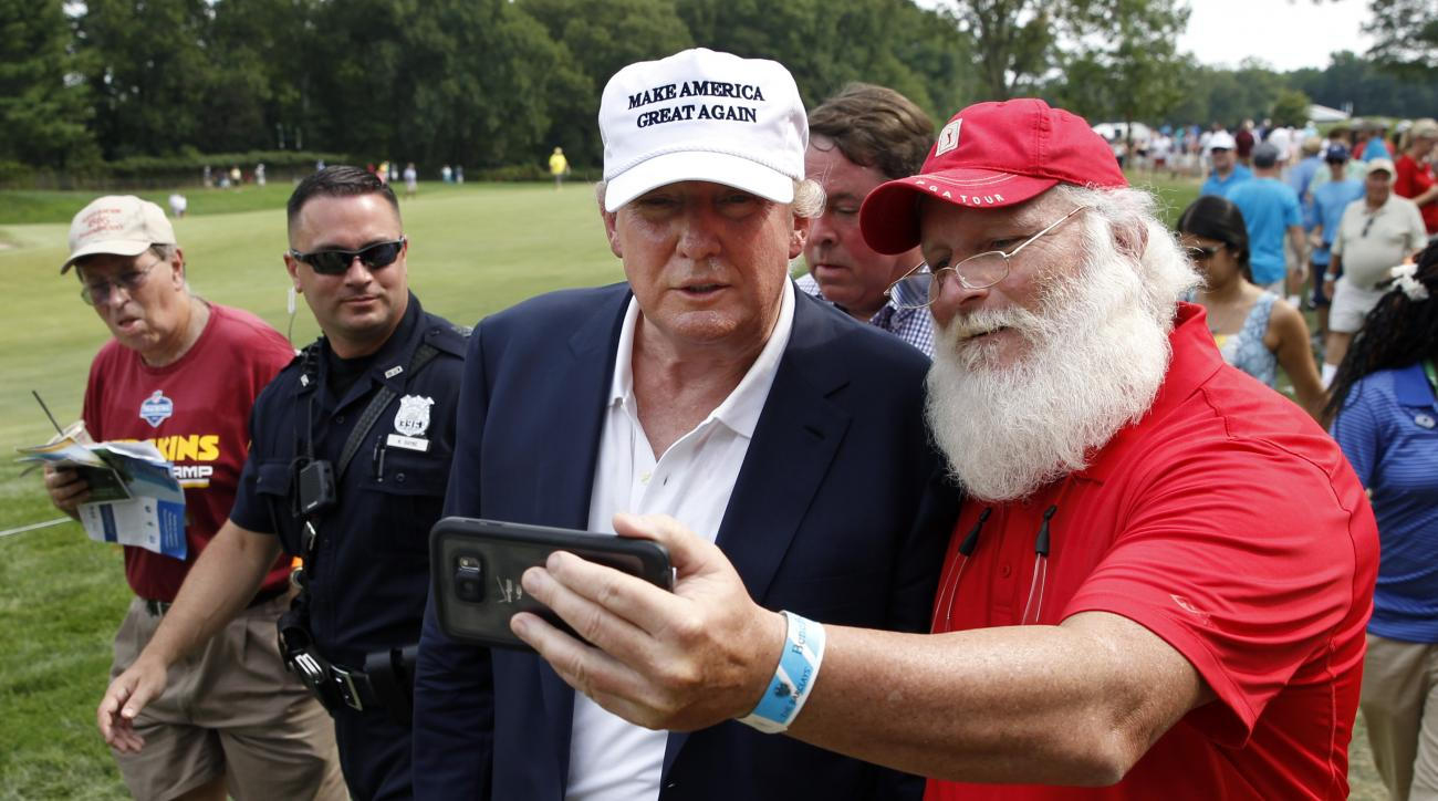 Republican presidential candidate Donald Trump, center, stops to take a photograph with Jim Tranz, of Port Charlotte, Fla., as he walks with a crowd during the final round of play at The Barclays golf tournament Sunday, Aug. 30, 2015, in Edison, N.J. (AP