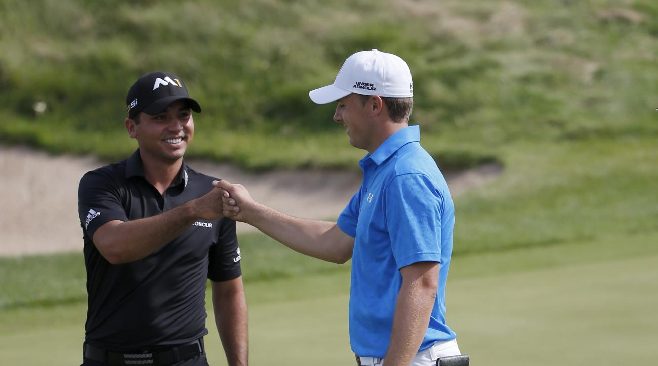 Jason Day, left, of Australia, fist bumps Jordan Spieth, after Spieth chipped in for birdie from off the green on the third hole during the first round of the BMW Championship golf tournament at Conway Farms Golf Club, Thursday, Sept. 17, 2015, in Lake Fo