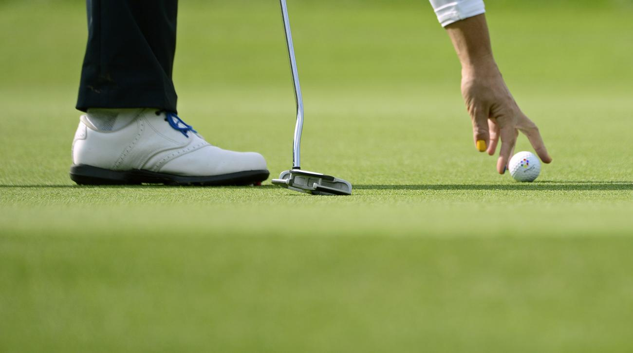 A European player places a ball in the foursomes on Day1 at the Solheim Cup golf tournament in St. Leon-Rot, southern Germany, Friday, Sept. 18, 2015. (AP Photo/Jens Meyer)