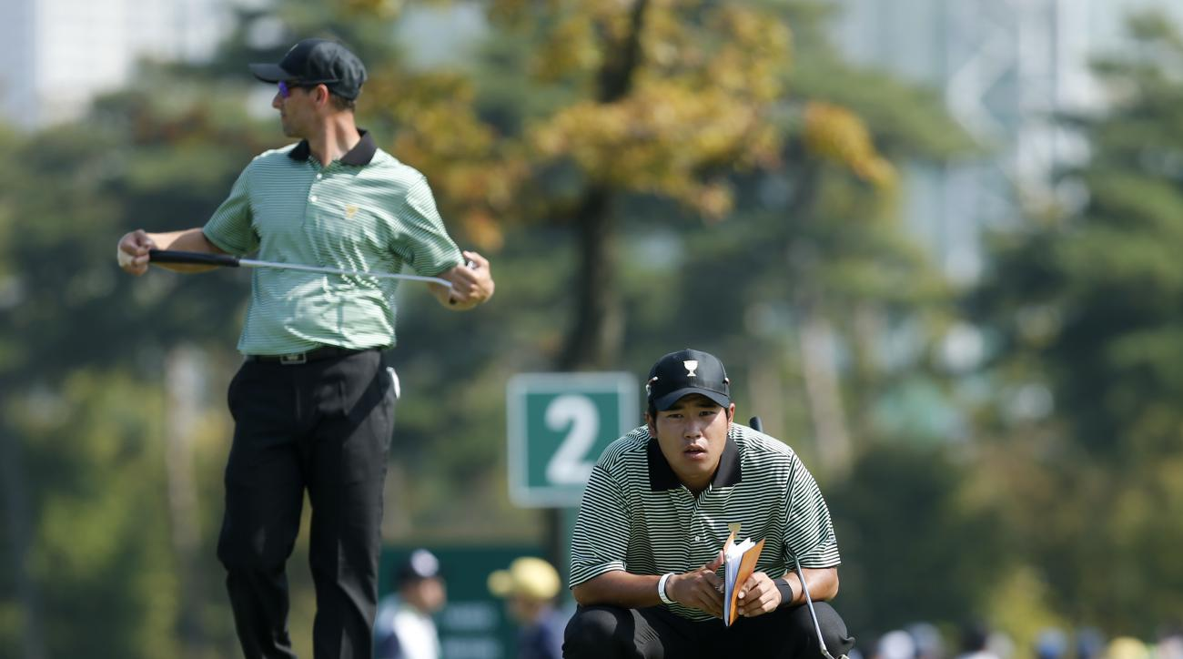 International team player Hedeki Matsuyama, right, of Japan and teammate Adam Scott of Australia prepare to putt during their foursome match at the Presidents Cup golf tournament at the Jack Nicklaus Golf Club Korea, in Incheon, South Korea, Thursday, Oct