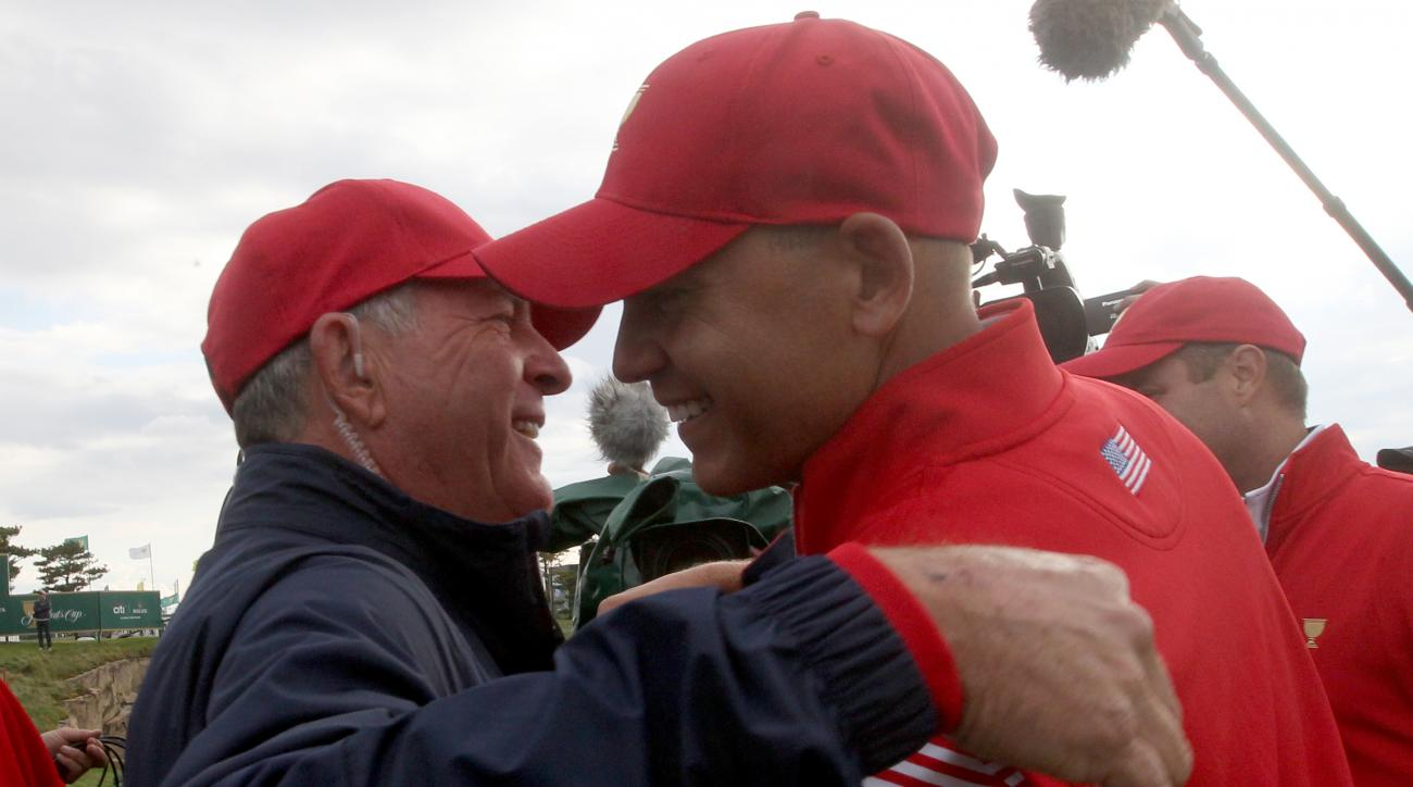 US team captain Jay Haas, left, embraces his son Bill after he won his singles match to defeat the International team to help retain the Presidents Cup golf at the Jack Nicklaus Golf Club Korea, in Incheon, South Korea, Sunday, Oct. 11, 2015.(AP Photo/Ahn