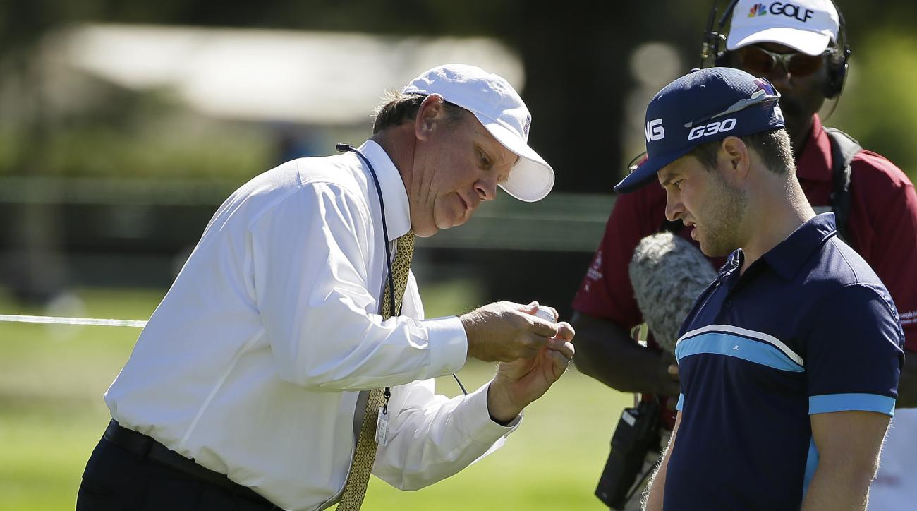 A rules official examines the ball of David Lingmerth, right, of Sweden, on the first green of the Silverado Resort North Course during the final round of the Frys.com PGA Tour golf tournament Sunday, Oct. 12, 2014, in Napa, Calif. (AP Photo/Eric Risberg)