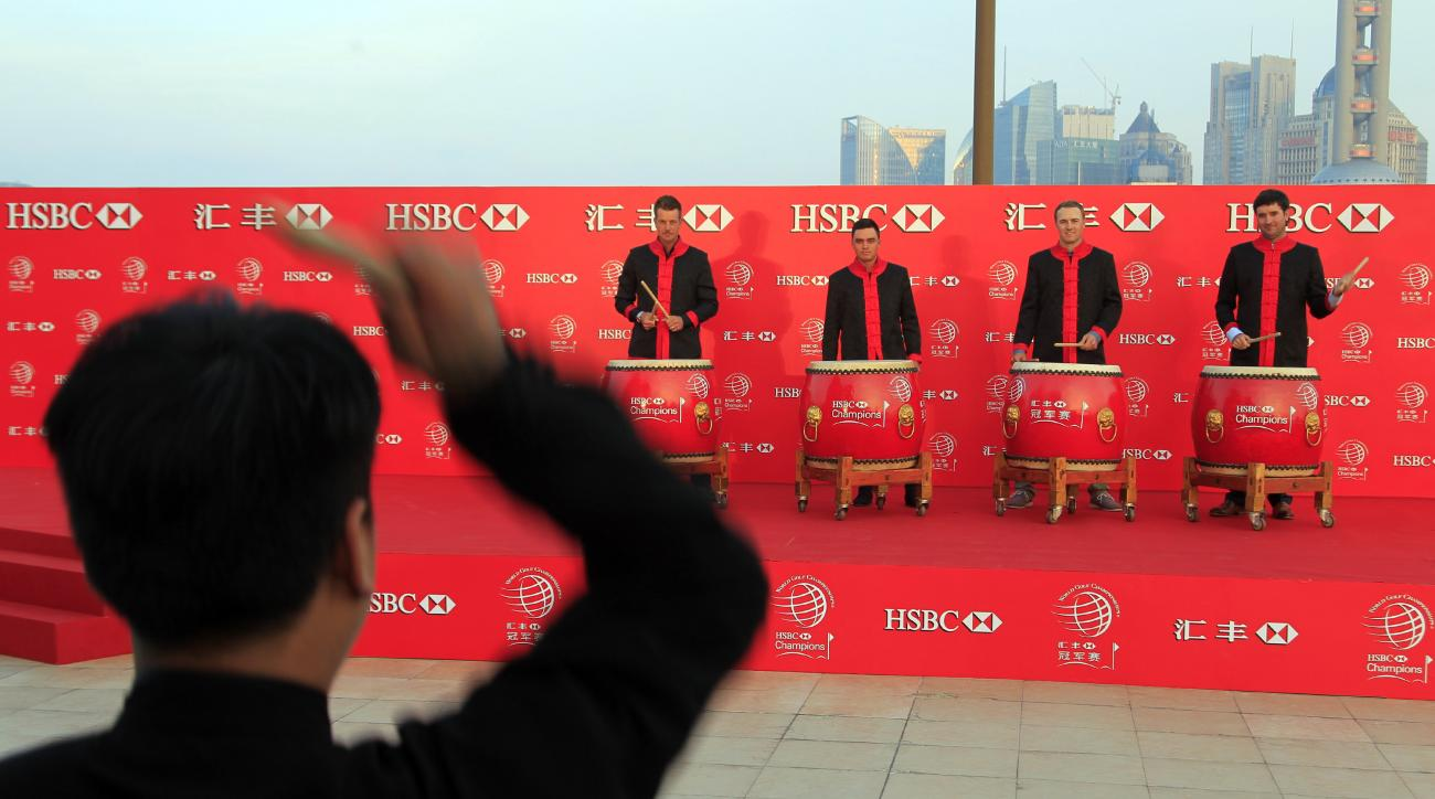 Golf players from back from left to right, Henrik Stenson, Rickie Fowler, Jordan Spieth and Bubba Watson, drum after a Chinese drummer during the HSBC Champions golf tournament photocall in Shanghai, China Thursday Nov. 3, 2015. (AP Photo)