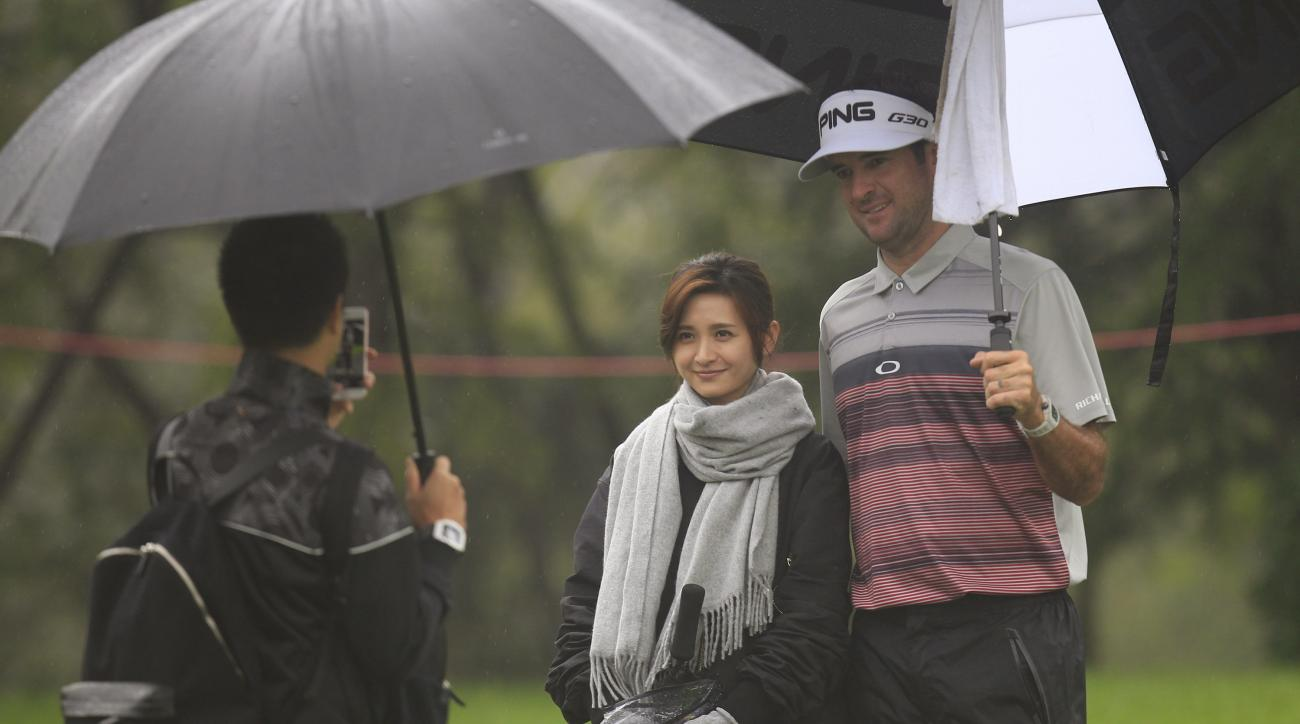 Bubba Watson of the United States, right, poses for a photo with a spectator on the 11th hole during the Pro-Am event of the HSBC Champions golf tournament at the Sheshan International Golf Club in Shanghai, China Wednesday Nov.4, 2015. (AP Photo)