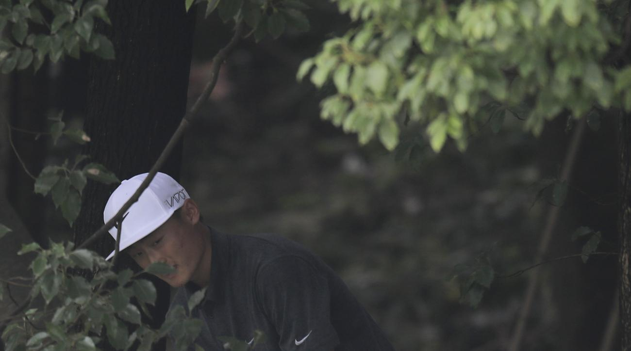 Li Haotong of China hits a shot from the bush on the 5th hole during the third round of the HSBC Champions golf tournament at the Sheshan International Golf Club in Shanghai, China Saturday, Nov. 7, 2015. (AP Photo)