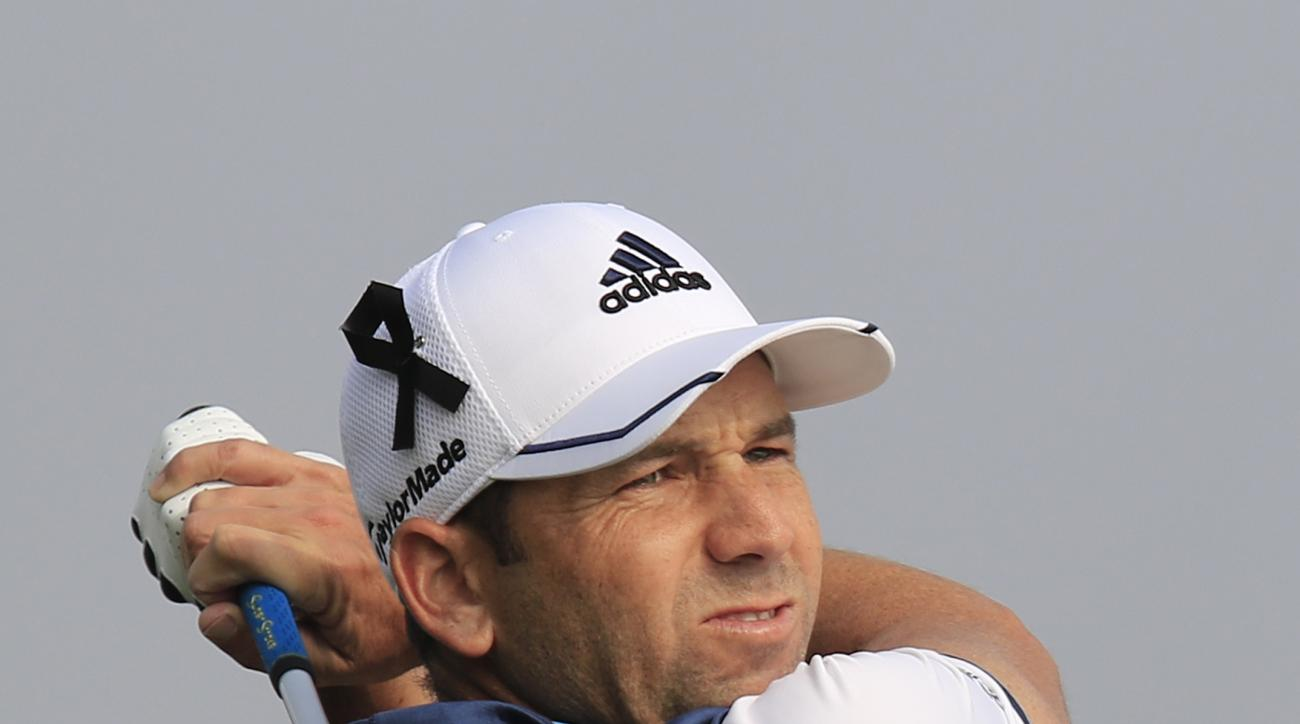 Sergio Garcia of Spain wearing a black ribbon on his hat to mourn for the victims killed in Friday's attacks in Paris, France, tees off on the 7th hole during the third round of the BMW Masters golf tournament at the Lake Malaren Golf Club in Shanghai, Ch