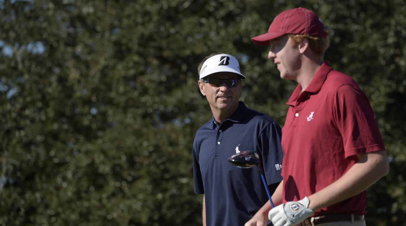 Davis Love III, left, and his son Dru Love walk down the second fairway after teeing off during the first round of the Father/Son Challenge golf tournament in Orlando, Fla., Saturday, Dec. 13, 2014.(AP Photo/Phelan M. Ebenhack)