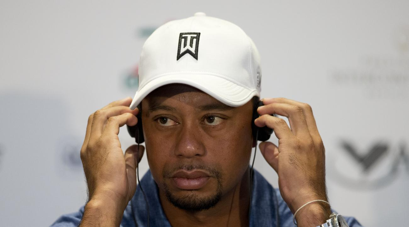 Tiger Woods listens through translation headphones during a press conference to launch the Bridgestone America's Golf Cup in Mexico City, Tuesday, Oct. 20, 2015. Woods withdrew from the Bridgestone America's Golf Cup and two other events he had planned to