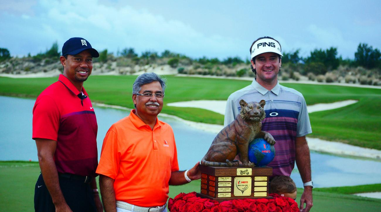 Bubba Watson, right, stands next to Hero Motorcycle Co. executive Pawan Munjal, center, and Tiger Woods, left, as they pose behind the Hero World Challenge trophy in Nassau, Bahamas, Sunday, Dec. 6, 2015. Watson, the winner of the Hero World Challenge by
