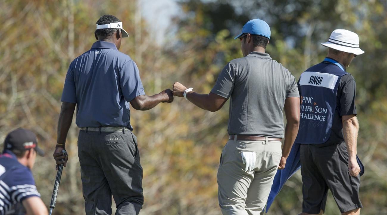 Vijay Singh, left celebrates with his son Qass Singh, right, during the first round of the Father/Son Challenge golf tournament in Orlando, Fla., Saturday, Dec. 12, 2015. (AP Photo/Willie J. Allen Jr.)