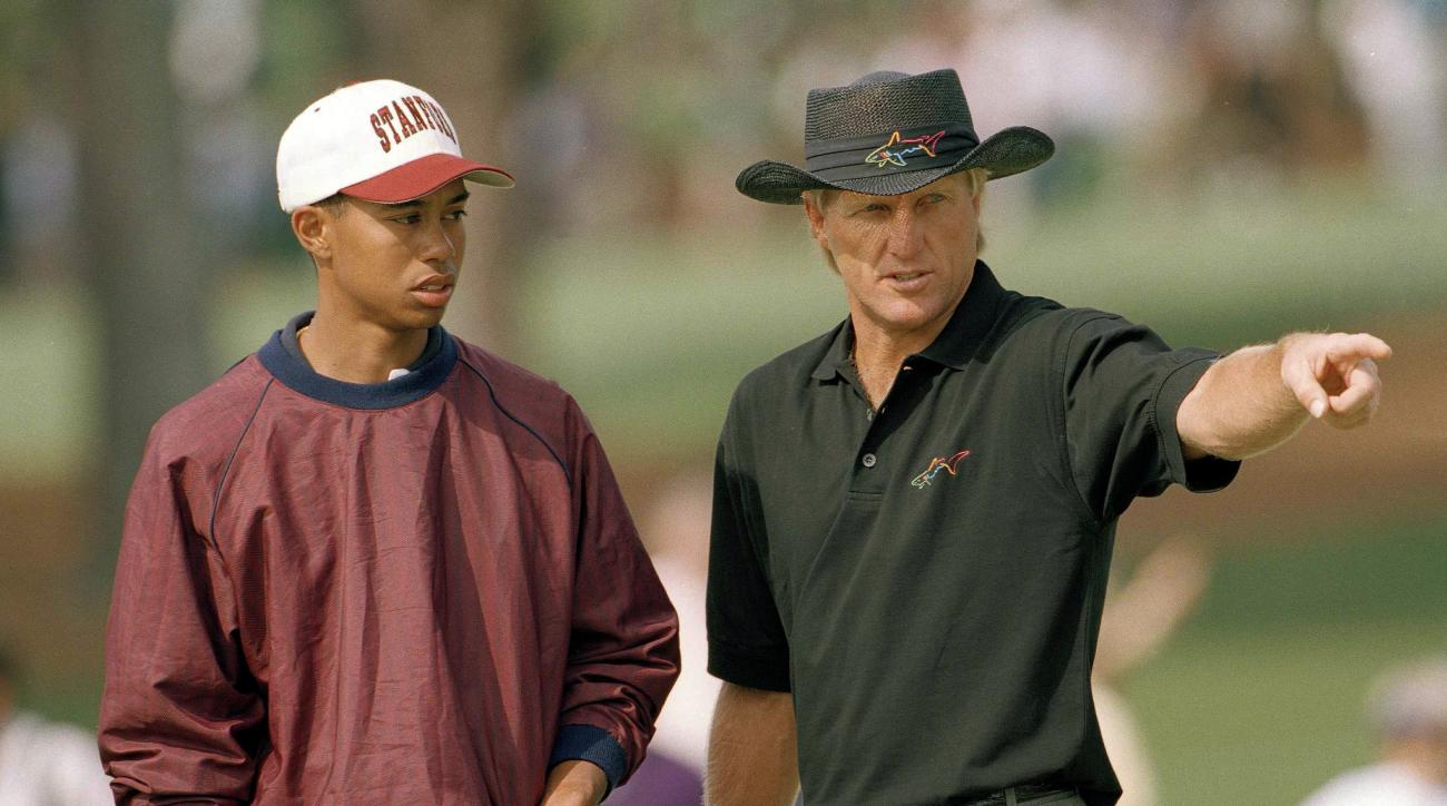 FILE - In this April 4, 1995, file photo, U.S. Amateur Champion Tiger Woods, left, talks with Greg Norman, of Australia, on the second hole during practice for the 1995 Masters golf tournament on the Augusta National Golf Club in Augusta, Ga. When Woods t