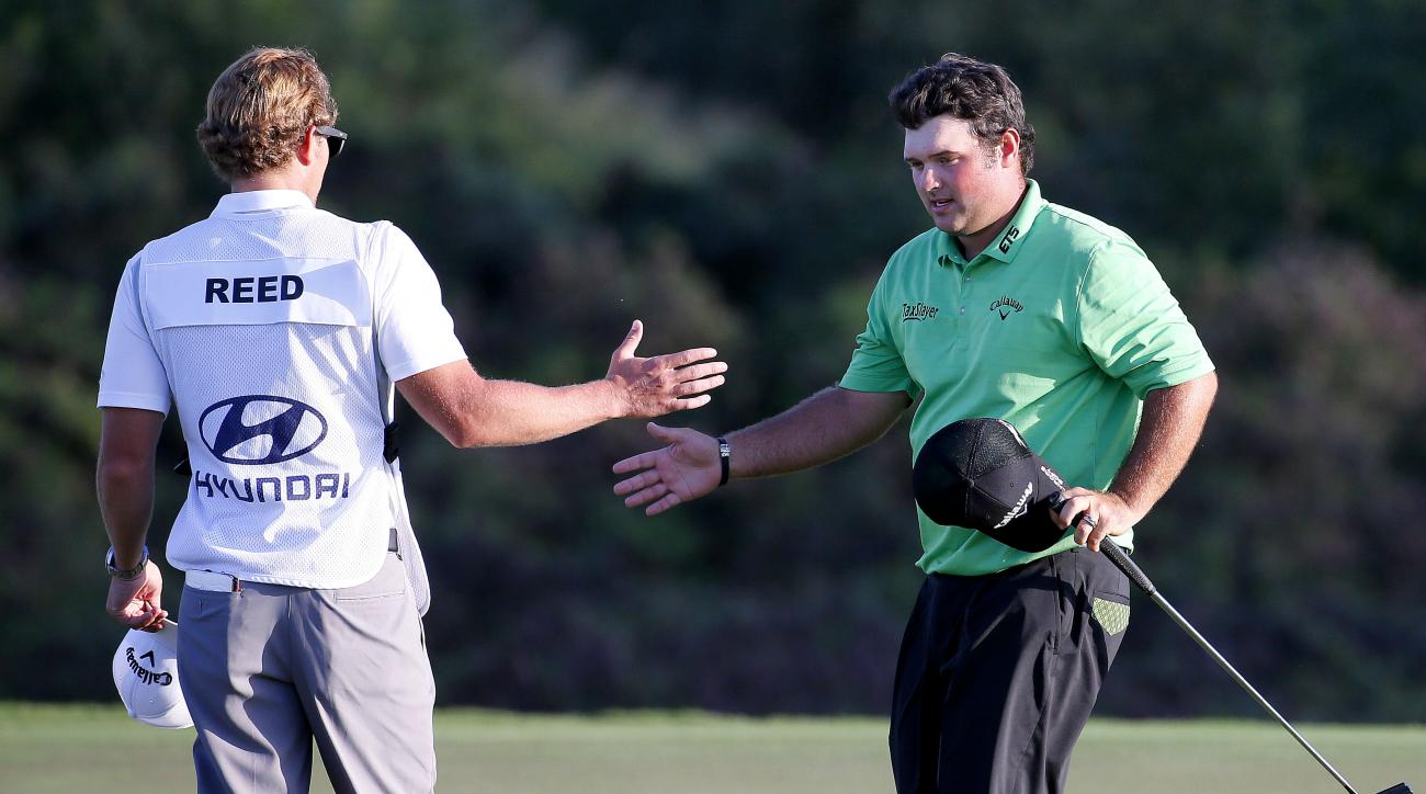 Patrick Reed greets his caddie after his eagle putt on the 18th green during the first round of the Tournament of Champions golf tournament Thursday, Jan. 7, 2016, at Kapalua Plantation Course on Kapalua, Hawaii. (AP Photo/Matt York)