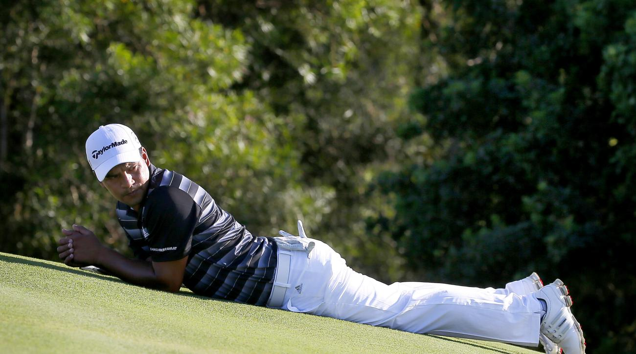 Fabian Gomez stretches his back on the 17th green during the final round of the Tournament of Champions golf tournament, Sunday, Jan. 10, 2016, at Kapalua Plantation Course on Kapalua, Hawaii. (AP Photo/Matt York)