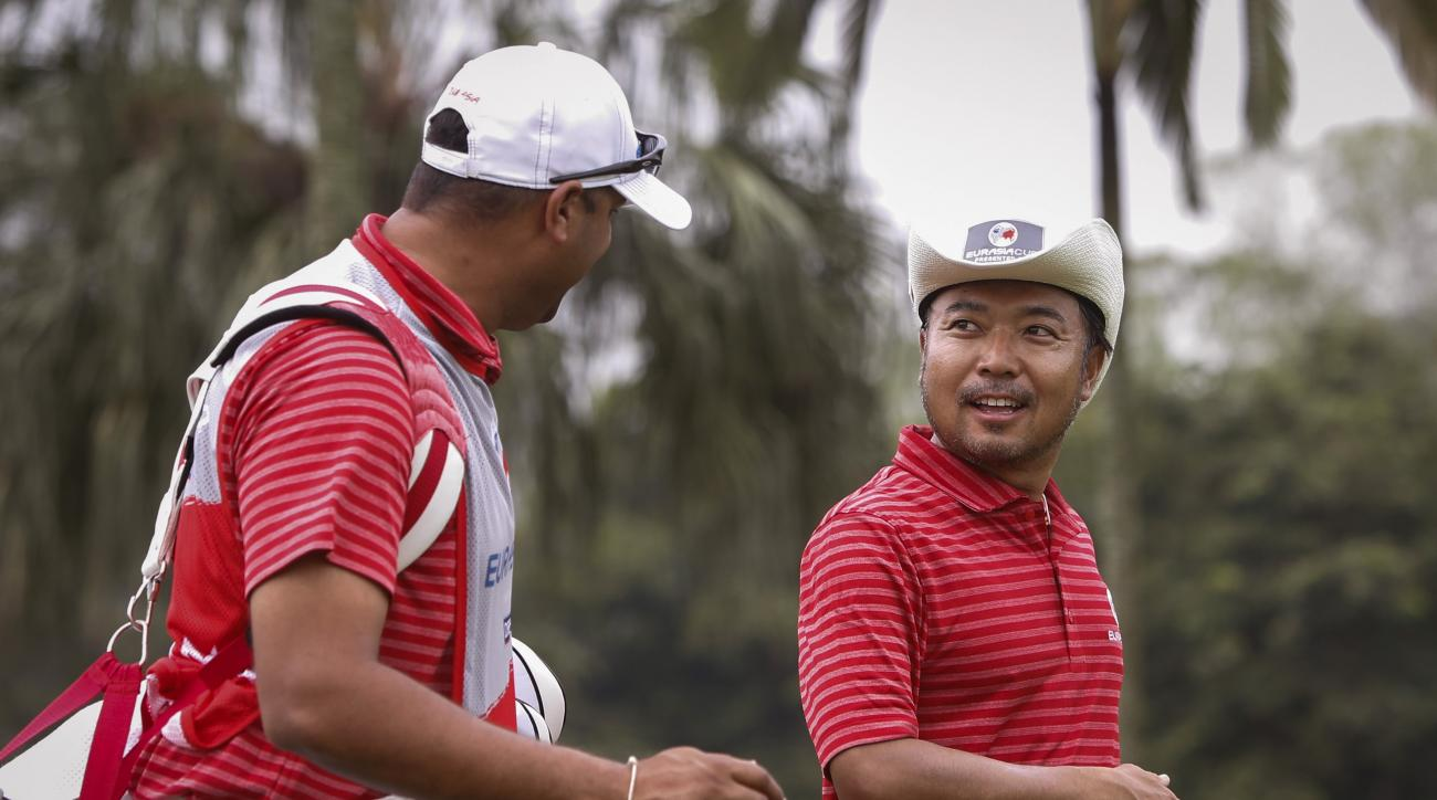 Japan's Shingo Katayama, right, speaks to his caddy as they walk towards the first hole's fairway during the second round of the EurAsia Cup golf tournament at the Glenmarie Golf and Country Club in Subang, Malaysia, Saturday, Jan. 16, 2016. (AP Photo/Jos