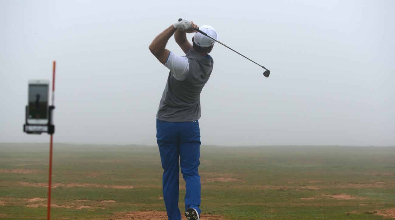 Trevor Immelman of South Africa records his swing on the practice range as the start of the already delayed round two of the Abu Dhabi HSBC Golf Championship from Friday was postponed again due to fog in Abu Dhabi, United Arab Emirates, Saturday, Jan. 23,
