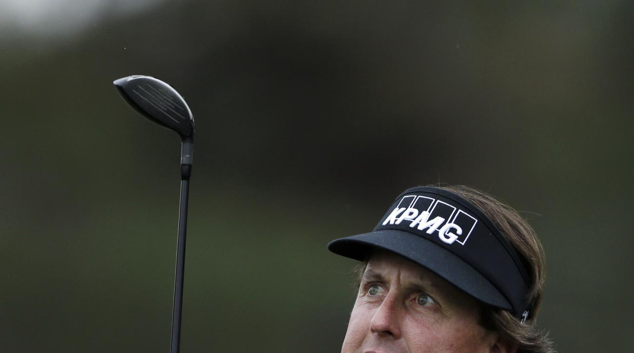 FILE - In this Jan. 24, 2013, file photo, Phil Mickelson grimaces as he watches his tee shot on the 10th hole of the north course at the Torrey Pines Golf Course during the first round of the Farmers Insurance Open golf tournament, in San Diego. The best