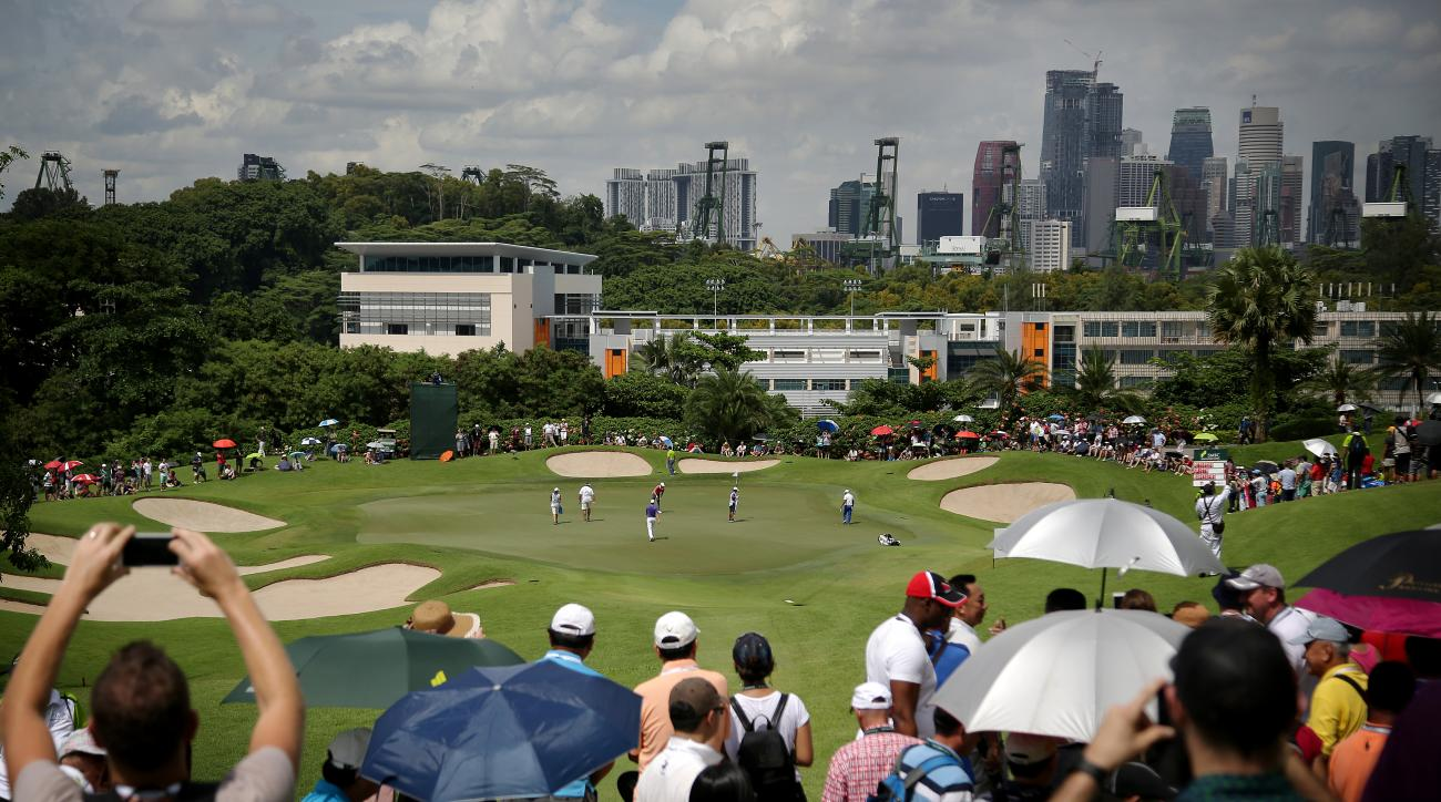 Spectators watch as Jordan Spieth approaches the second hole with the Singapore financial district seen in the background, during the third round of the SMBC Singapore Open golf tournament at Sentosa Golf Club's Serapong Course on Saturday, Jan. 30, 2016,