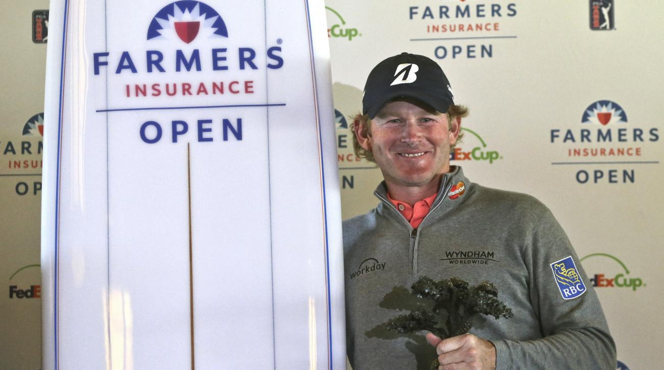 Brandt Snedeker holds the Framers Insurance Open trophy and a ceremonial surfboard after the final round of the Farmers Insurance Open golf tournament  Monday, Feb. 1, 2016, in San Diego. Snedeker finished his final round Sunday before it was suspended be