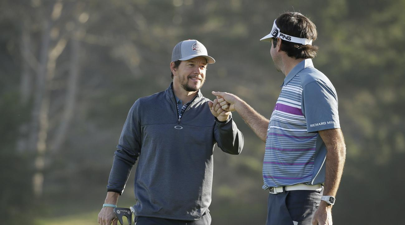 Bubba Watson, right, is greeted by playing partner Mark Wahlberg, left, after making a birdie on the second green of the Spyglass Hill Golf Course during the first round of the AT&T Pebble Beach National Pro-Am golf tournament Thursday, Feb. 11, 2016, in