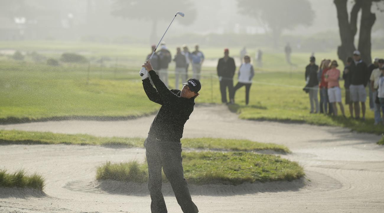 Phil Mickelson follows his shot out of a bunker on the sixth fairway of the Monterey Peninsula Country Club Shore Course during the second round of the AT&T Pebble Beach National Pro-Am golf tournament Friday, Feb. 12, 2016, in Pebble Beach, Calif. (AP Ph