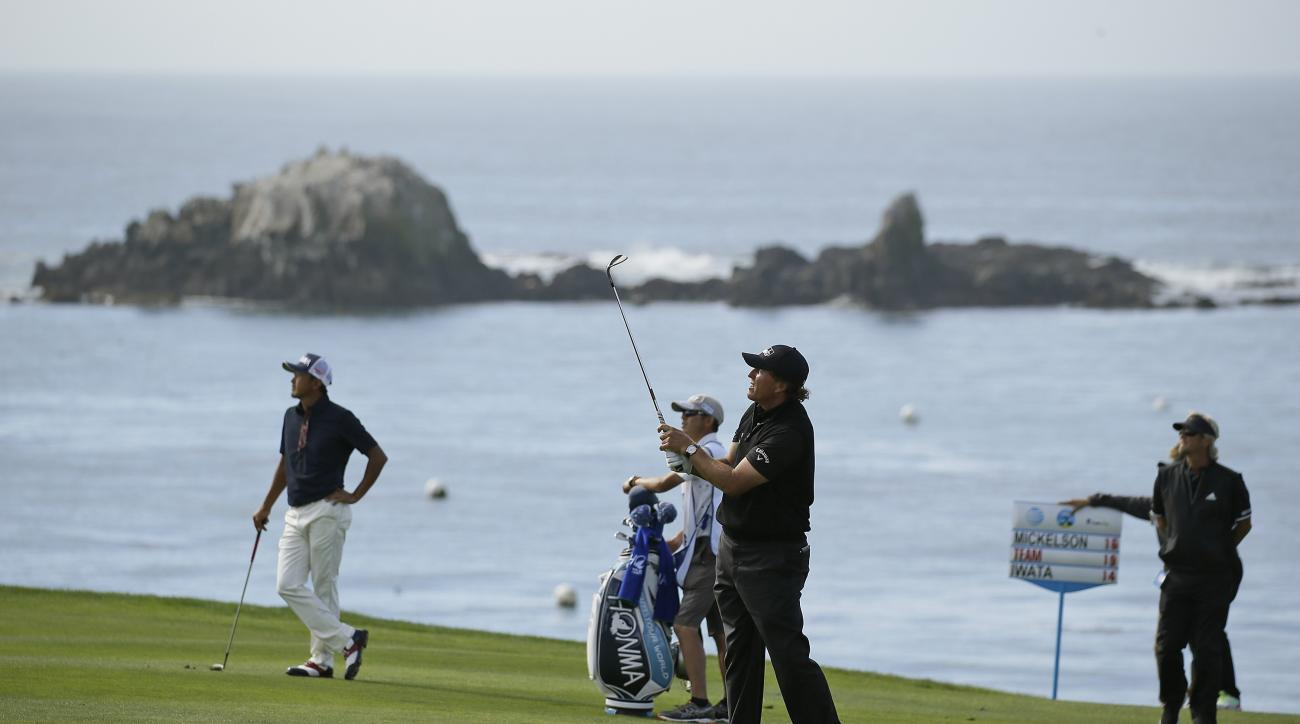 Phil Mickelson, foreground, follows his shot from the fourth fairway of the Pebble Beach Golf Links during the final round of the AT&T Pebble Beach National Pro-Am golf tournament Sunday, Feb. 14, 2016, in Pebble Beach, Calif. Hiroshi Iwata, of Japan, loo