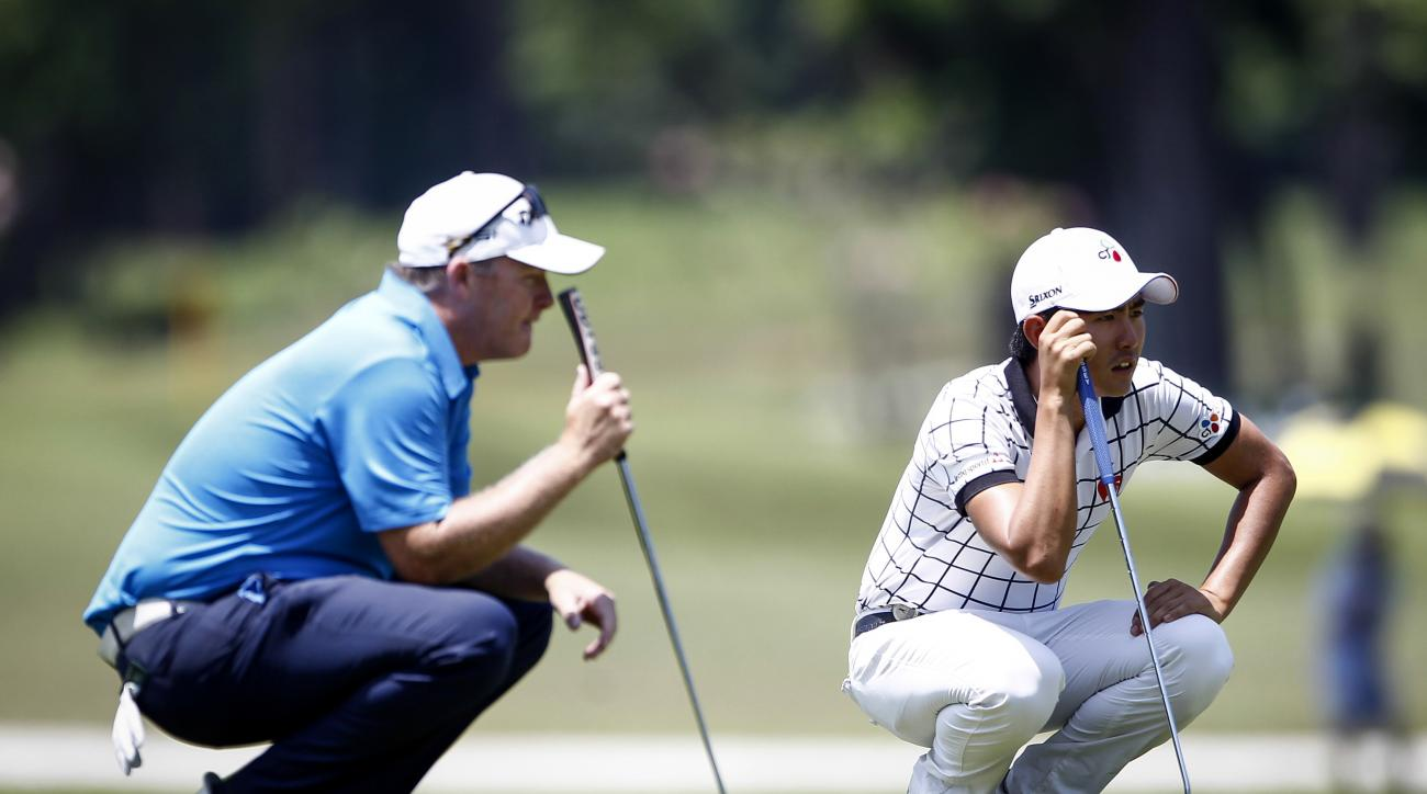 Marcus Fraser, left, of Australia and Lee Soo-min of South Korea wait for their turn on the 11th green during the final round of the Maybank Championship golf tournament in Kuala Lumpur, Malaysia, on Sunday, Feb. 21, 2016. (AP Photo/Joshua Paul)