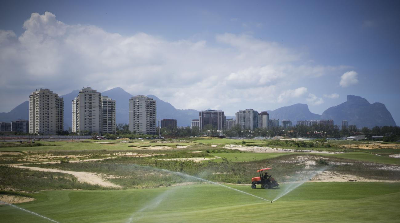 FILE - In this March 25, 2015, file photo, a worker cuts the grass on the Olympic Golf course in Rio de Janeiro, Brazil. PGA Commissioner Tim Finchem had a free charter lined up for the best players in the world to jet down to Brazil, play 18, and head ba