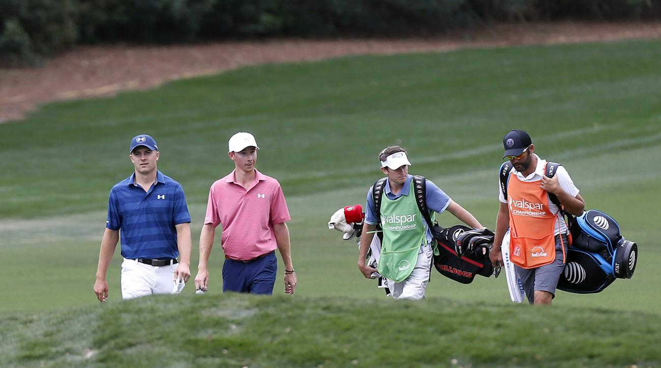 Jordan Spieth, left, and Lee McCoy, walk ahead of their caddies along the first fairway during the final round of the Valspar Championship golf tournament Sunday, March 13, 2016, in Palm Harbor, Fla. (AP Photo/Brian Blanco)